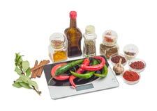 Peperoncino rosso sulla scala della cucina e varie spezie, erbe e salsa Fotografia Stock