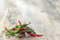 Peperoncino rosso verde e rosso, sulla tavola di legno, ingrediente di erbe importante in molti generi di alimento della spezia,  immagine stock libera da diritti