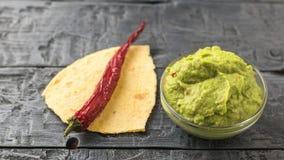 Peperoncino sui pezzi di pita e di guacamole fresco in ciotola sulla tavola Avocado messicano vegetariano dell'alimento di dieta immagini stock libere da diritti