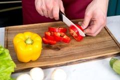 Peperone della fetta della mano con il coltello ceramico Fotografia Stock Libera da Diritti