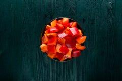 Peperone dolce affettato in una ciotola di legno sulla tavola di legno scura Fotografie Stock