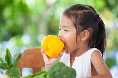 Peperone dolce mordace della ragazza asiatica del bambino ed imparare circa la verdura fotografie stock