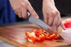 Peperone dolce rosso che è tagliato da un coltello su un bordo di legno Immagine Stock Libera da Diritti