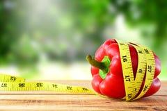 Peperone dolce rosso con nastro adesivo di misurazione giallo, concetto di dieta immagini stock