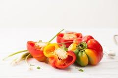 Peperoni affettati crudi variopinti a metà dolci e cipolle verdi Fotografia Stock