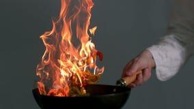 Peperoni che sono lanciati in un wok ardente archivi video