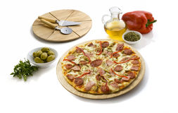 Peperoni and cheese pizza. Pepperoni and cheese pizza isolated on white, has a cutting table and some ingredients all around royalty free stock photography