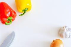 Peperoni, cipolla, aglio e coltello rossi e gialli su un fondo bianco, vista superiore Immagine Stock