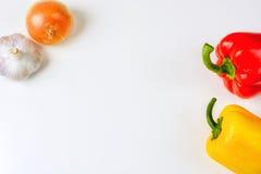 Peperoni, cipolla ed aglio rossi e gialli su un fondo bianco, vista superiore Fotografia Stock