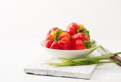 Peperoni crudi variopinti dolci, cipolle verdi in ciotola bianca Fotografie Stock