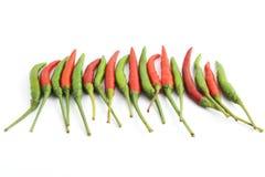 Peperoni di peperoncini rossi rossi e verdi su bianco Fotografia Stock