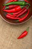 Peperoni di peperoncino rosso caldo in ciotola di legno sopra tela di canapa Immagine Stock