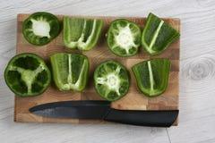 Peperoni dolci affettati con un coltello ceramico su un bordo di legno Fotografie Stock Libere da Diritti