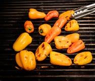 Peperoni dolci carbonizzati che cucinano su una griglia Fotografie Stock
