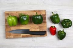 Peperoni dolci con un coltello ceramico su un bordo di legno Immagini Stock Libere da Diritti