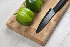 Peperoni dolci con un coltello ceramico su un bordo di legno Fotografia Stock
