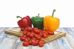Peperoni dolci e pomodori del bambino su un fondo di bianco del tagliere Fotografia Stock