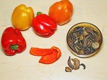 Peperoni dolci freschi e fungo secco sul bordo di legno Fotografie Stock Libere da Diritti