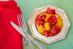 Peperoni dolci fritti gialli rossi cucinati su un piatto d'argento Forcella e coltello e tovagliolo rosso Vecchia tabella immagini stock