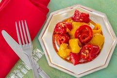 Peperoni dolci fritti gialli rossi cucinati su un piatto d'argento Forcella e coltello e tovagliolo rosso Vecchia tabella immagine stock libera da diritti