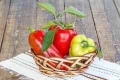 Peperoni dolci rossi e gialli maturi in un canestro di vimini su spirito dell'asciugamano Fotografia Stock Libera da Diritti