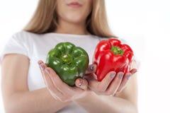 Peperoni dolci rossi e verde tenuto dalla giovane donna Alimento vegetariano Cottura dell'ingrediente e cibo sano Fotografia Stock Libera da Diritti