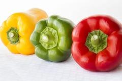 Peperoni dolci rossi e verdi e gialli in una fila su fondo bianco Fotografia Stock