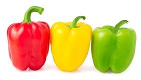 Peperoni dolci rossi, gialli e verdi su un fondo bianco Immagine Stock