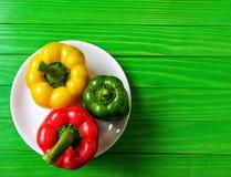 peperoni dolci variopinti su un piatto bianco della porcellana su un fondo di legno verde Fotografie Stock Libere da Diritti