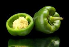 Peperoni dolci verdi divisi in due primo piano isolati sul nero Fotografie Stock Libere da Diritti