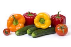 Peperoni gialli ed arancio rossi con i pomodori su un fondo bianco Cetrioli con i peperoni variopinti in composizione su un backg Immagine Stock Libera da Diritti