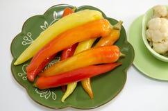 Peperoni marinati su un piatto verde isolato Fotografia Stock Libera da Diritti