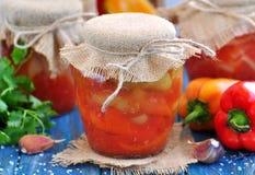 Peperoni marinati in succo di pomodoro con le cipolle, l'aglio ed il basilico Fotografia Stock