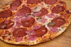 Peperoni- och skinkapizza Arkivfoto