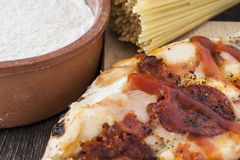 Peperoni pizza, flour and a bunch of spaghetti Stock Image