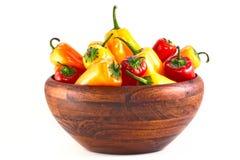 Peperoni rossi e gialli in una ciotola di legno Fotografia Stock