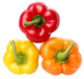 Peperoni rossi, gialli ed arancio isolati sui precedenti bianchi Fotografie Stock