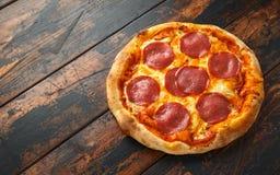Peperoni salamipizza på trätabellen ordna till f?r att ?ta arkivbilder
