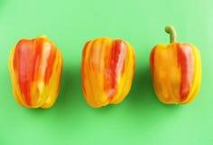 3 peperoni a strisce che mettono su fondo verde Fotografia Stock