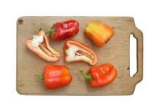 Peperoni sulla scheda di taglio della cucina isolata Fotografia Stock
