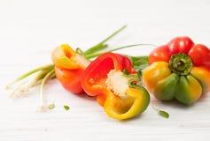 Peperoni variopinti dolci crudi del mezzo taglio su bianco Immagini Stock Libere da Diritti
