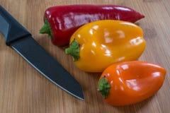 Peperoni variopinti sul tagliere con il coltello Immagine Stock