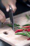 Peperoni verdi e rossi del chilie che sono tagliati su un bordo di legno Immagini Stock