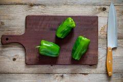 Peperoni verdi sul tagliere di legno Fotografie Stock