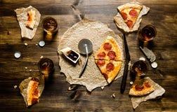 Peperonipizza och öl för fyra personer På en trätabell royaltyfria bilder