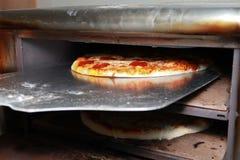 Peperonipizza som kommer ut ur ugnen Arkivbilder