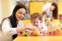 Pepiniera nauczyciel i dziecko bawić się z rozwojowymi zabawkami w preschool zdjęcia stock