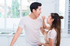 Pepino de alimentação da mulher a equipar como amantes ou pares na sala da cozinha Conceito do cozimento e da lua de mel e do cas foto de stock