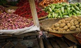 Pepino de la patata de la cebolla roja y chiles rojos con la cesta de madera de bambú en mercado tradicional en Bogor Indonesia Imagen de archivo libre de regalías