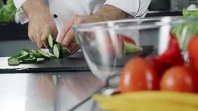 Pepino del corte del cocinero del hombre en el restaurante de la cocina Mano del cocinero que prepara la ensalada fresca almacen de metraje de vídeo